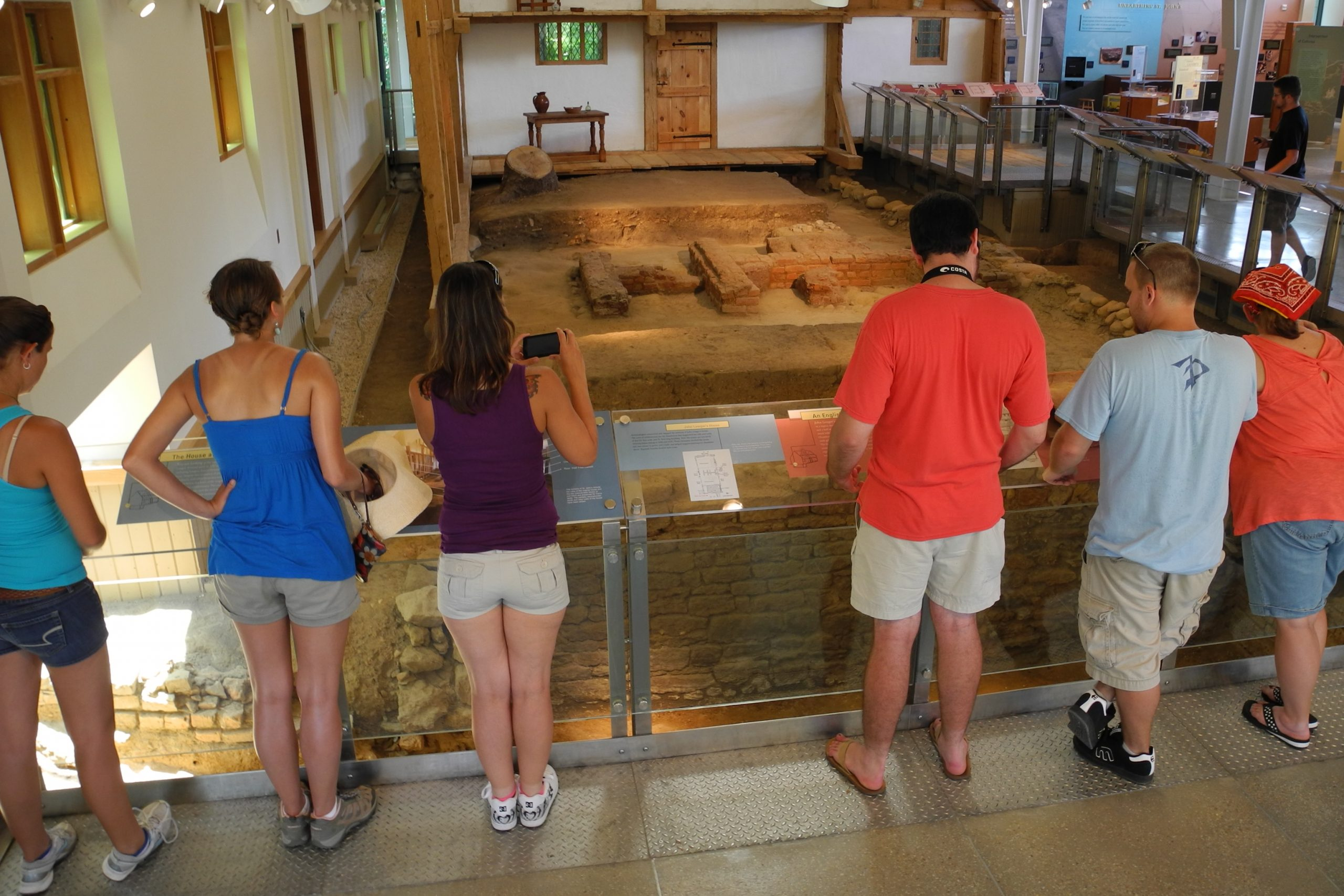 A group of visitors looks at the archaeological remains of house built in the 1600's