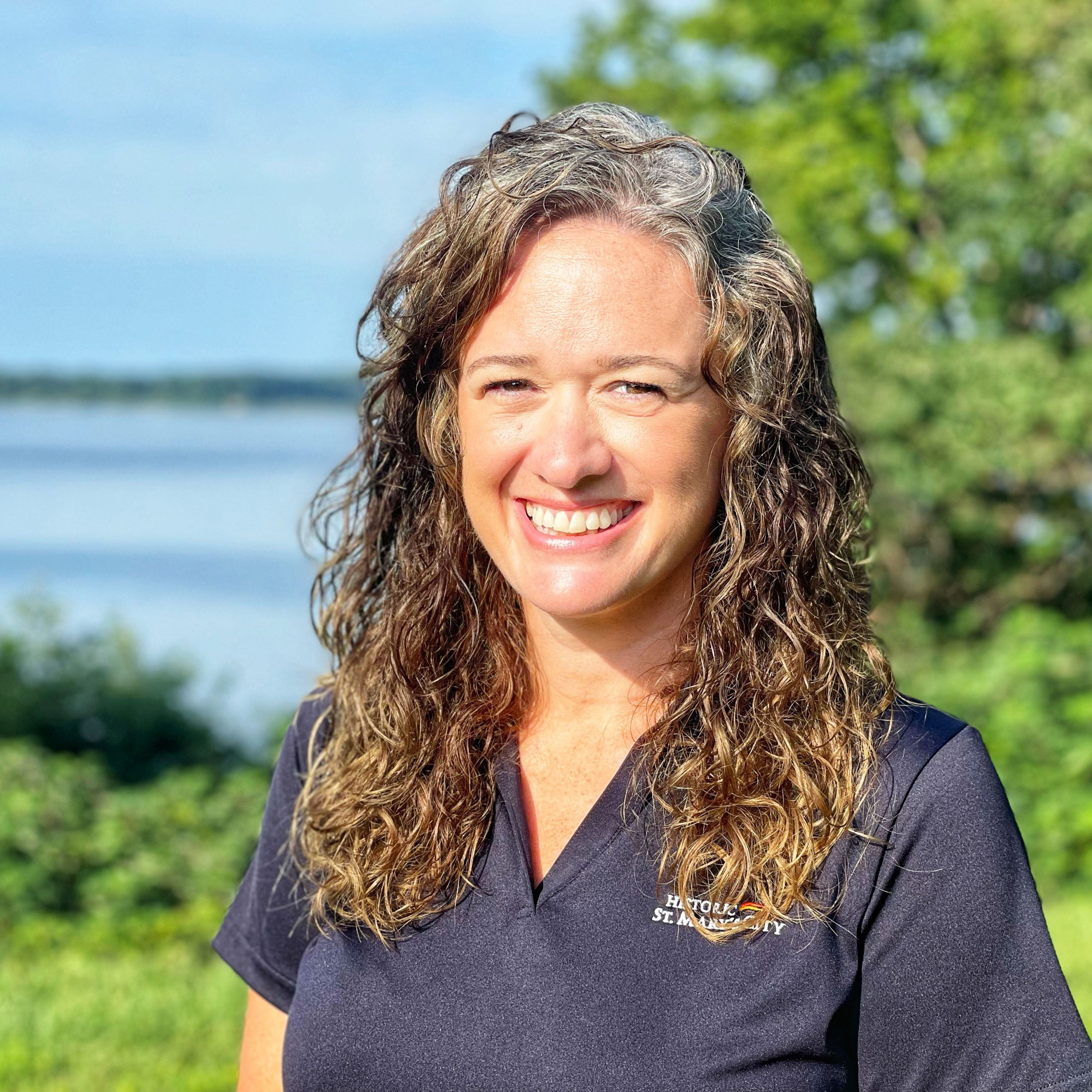 Volunteer Coordinator Ellen Fitzgerald stands, smiling, with the St. Mary's River behind her.